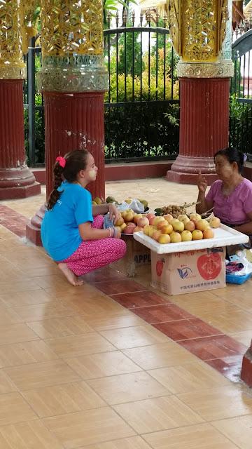 Macarena comprando manzanas a las puertas de Kyauktawgyi Paya