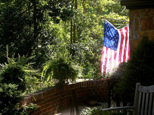 Glowing American flag is backlit by setting sun next to front door. Pots of fern grace the porch.