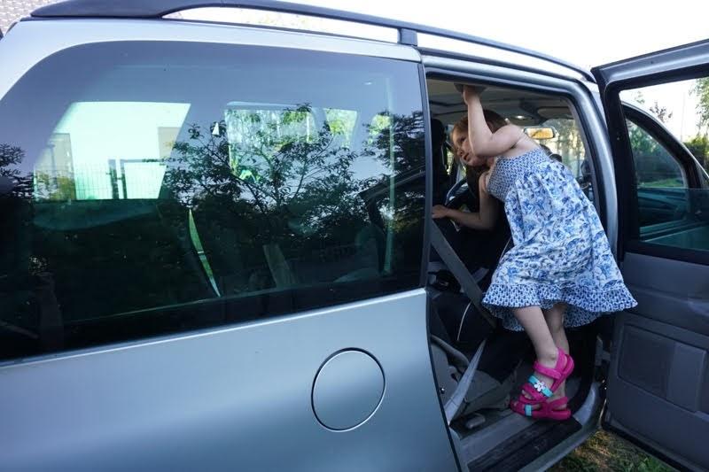 dziecko wsiada do auta minivan, 3 foteliki w aucie