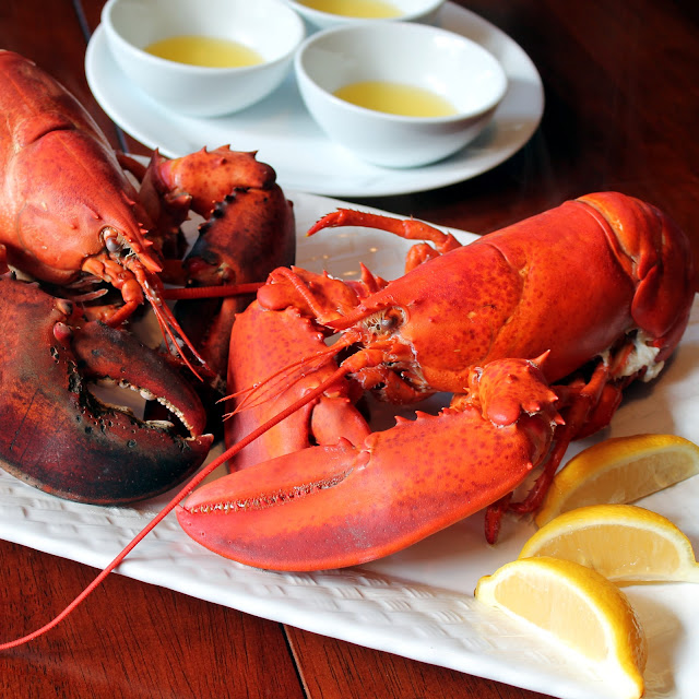 Lobster is served on a platter with fresh lemon and dipping butter