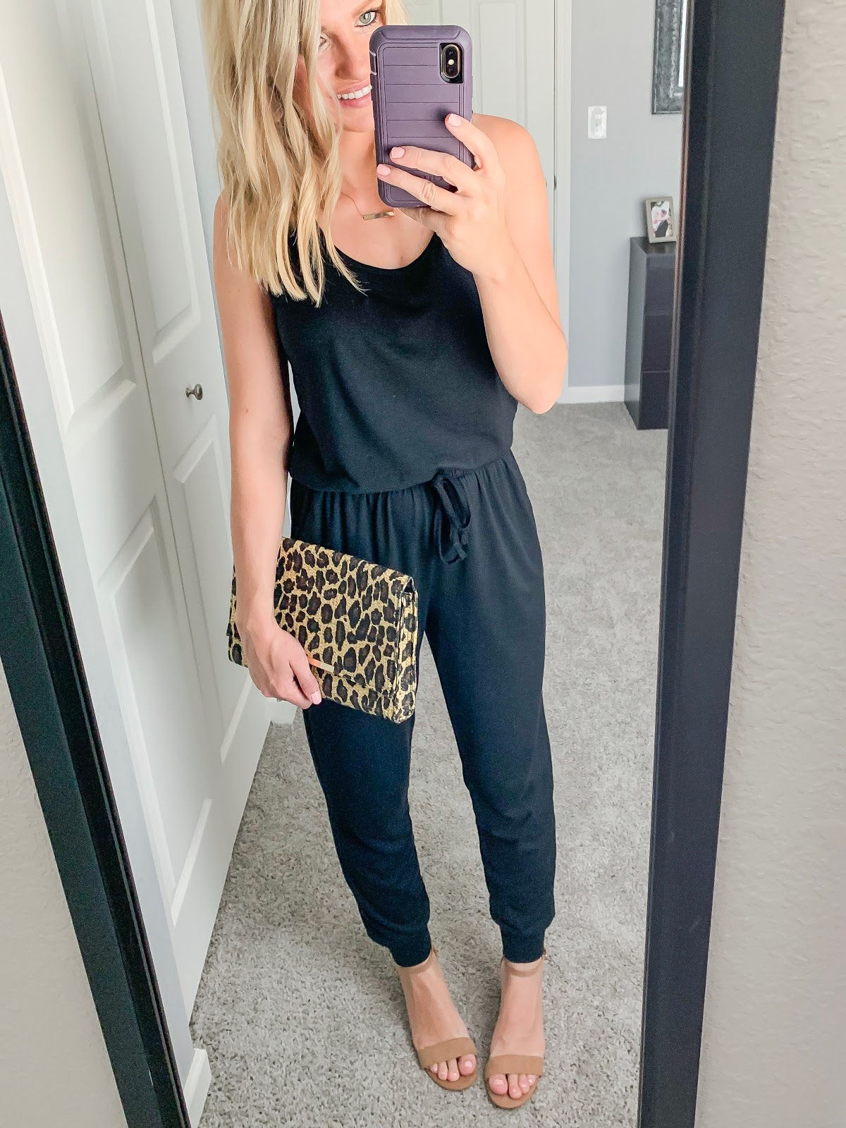 Black jumpsuit styled with a leopard clutch