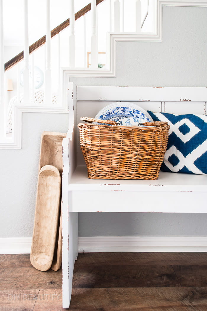 farmhouse bench, dough bowls and basket filled with dishes