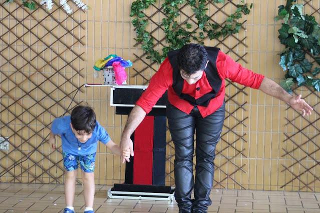 Artista de Humor e Circo se apresentando com criança do público, participando do show em evento do dia das crianças.