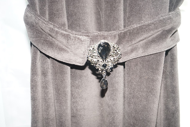 Gray velvet curtain with brooch on tie back