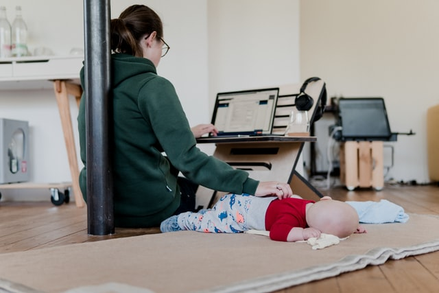 mulher em seu home office acariciando seu bebê