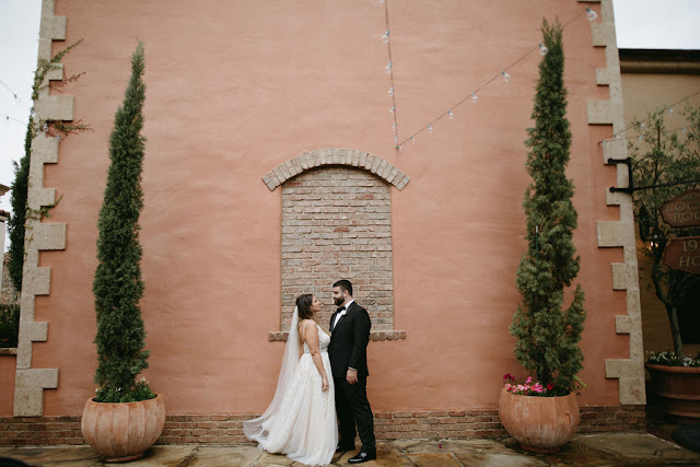 bride and groom in front of large wall