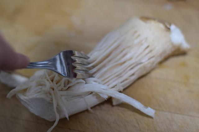 Shredding the eryngii mushroom with a fork.