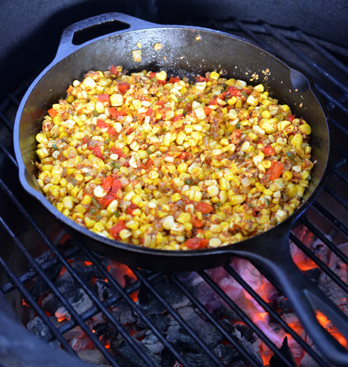 corn and peppers in a cast-iron skillet on the grill