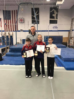 Man standing with three young boys at a gym holding awards