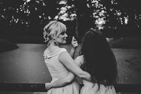 Black and whitee photo of a blonde woman and a woman with long, dark hair hugging and outside