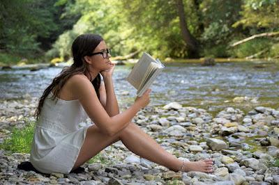 perempuan membaca buku di sungai