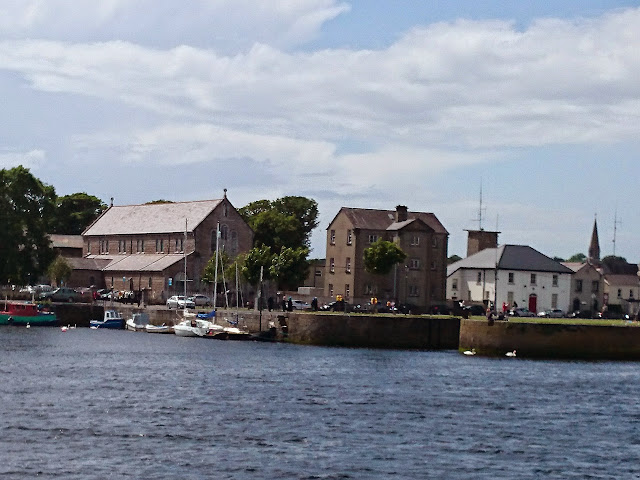 Photo of Claddagh Church, former National School buidling and Creaven House, with the fire station training tower and steeple of the Jesuit church in the background, and the River Corrib and various small boats in the foreground.   Sunny day.