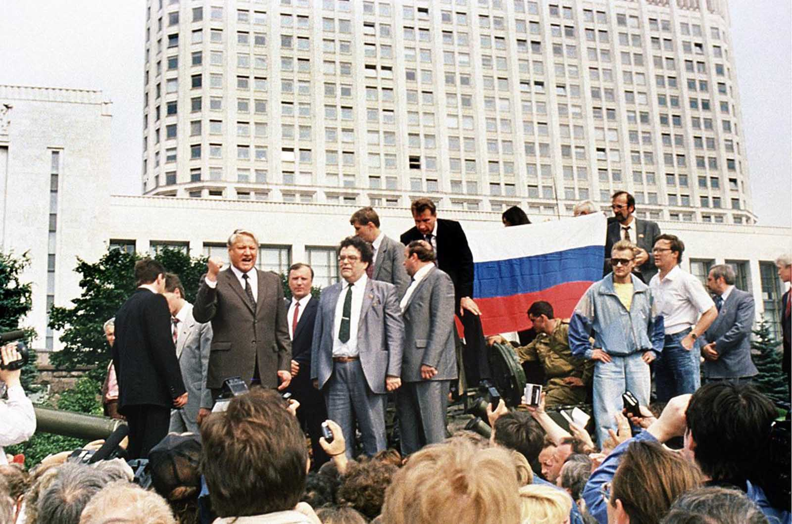 Russian President Boris Yeltsin (left) stands on top of an armored vehicle parked in front of the Russian Federation building as supporters hold a Russian federation flag on August 19, 1991, during a coup attempt. Yeltsin addressed a crowd of supporters calling for a general strike.