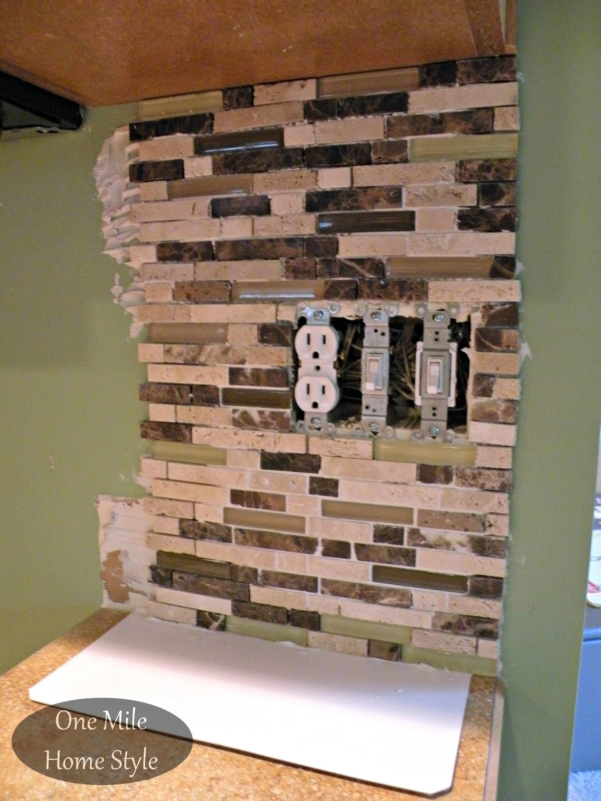 First section of backsplash tiles up on the wall