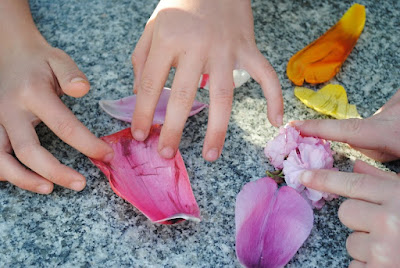 children's hands and flower petals
