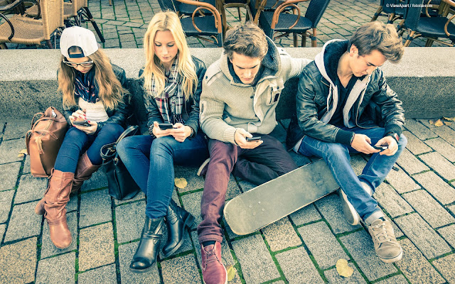 Stock photo of young adults using smart phones by ViewApart.