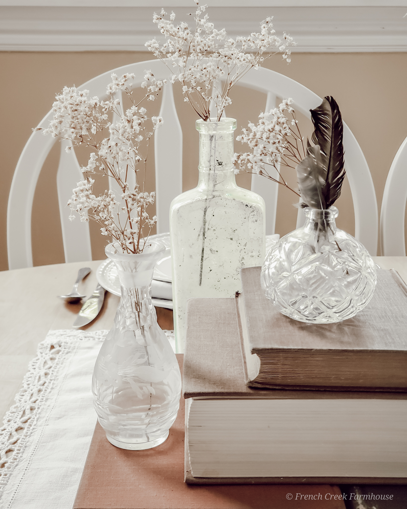 Small vintage glass bottles and vases filled with baby's breath