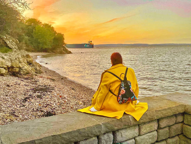 Plus size travel blogger The Owlet sitting on the beach at sunset