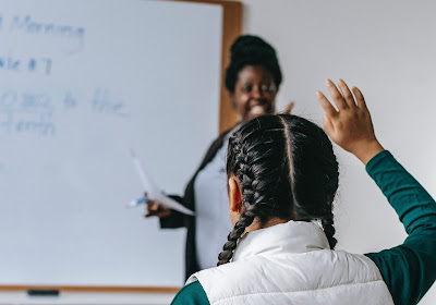 Photo of a girl sitting in a classroom raising her hand while the teacher points to her