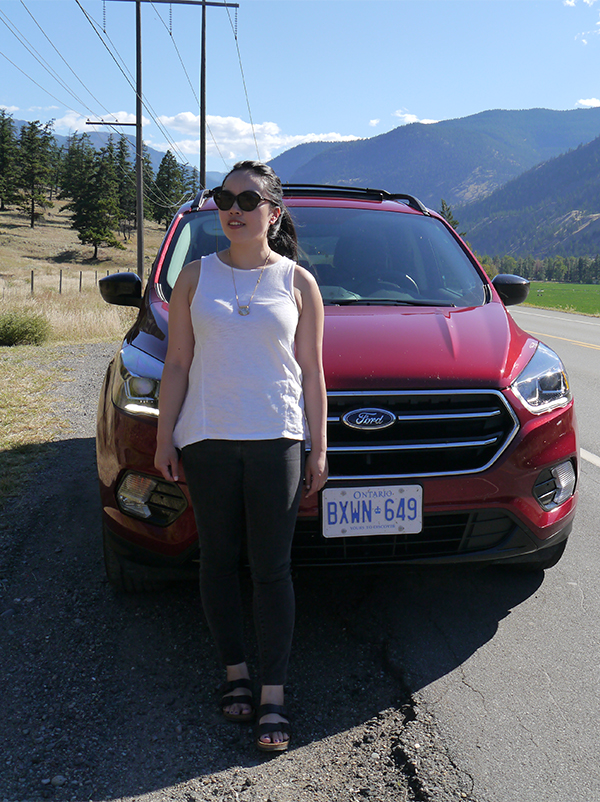 Vancouver beauty and lifestyle blogger Solo Lisa stands in front of a 2016 cherry red Ford Escape in the Similkameen Valley, during the drive from Naramata bench back to Vancouver.