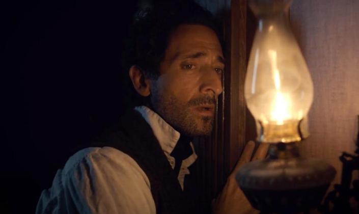 Imagem: o personagem interpretado por Adrian Brody, um homem branco de nariz longo e cabelos pretos em roupas de época, carregando uma lamparina acesa em um tipo de porão.