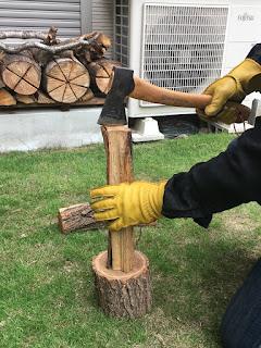 斧と薪を台に叩きつけるように落とす