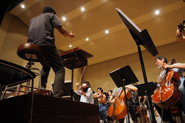 orchestra with a single unit conductor controlling and managing a large ensemble