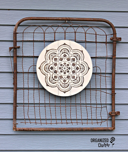 Photo of wooden clock face stenciled with mandala