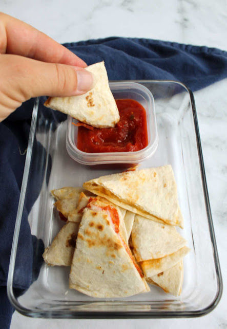 hand dipping wedge of quesadilla into small container of pizza sauce