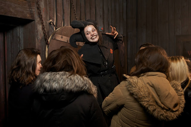 A photograph of a woman dressed in dark jester costume with black lipstick and eye makeup, standing on a box with her arms stretched wide, while a group of visitors watch her with their backs to the camera