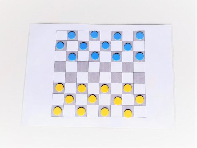 zdjęcie przedstawia wydrukowaną planszę do gry w warcaby 8x8 oraz początkowe ustawienie 12 pionków w kolorze niebieskim oraz 12 w kolorze żółtym