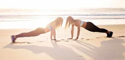 two girl doing the exercise at beach