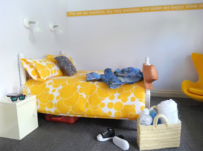 One-twelfth scale modern miniature bedroom in yellow, white and grey. On the bed is a hawaiian and baseball cap. On the floor in front is a pair of sneakers and a cane basket containing a towel, book and bottle of water.