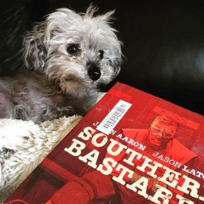 Murchie lies on a fuzzy beige pillow. In front of him is a trade paperback copy of Southern Bastards Volume Two. Its red-tinted cover features a young white man seated in a locker room. Band aids cross his nose and forehead.