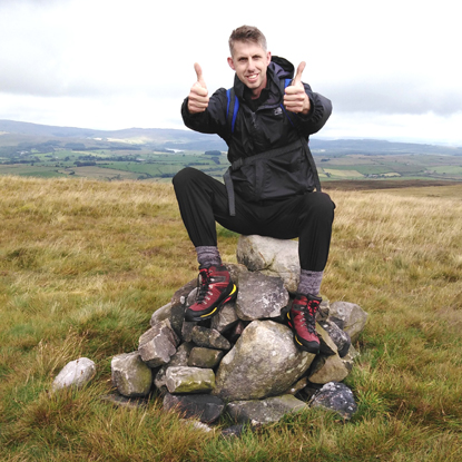 man sitting on pile of rocks on top of hill and giving two thumbs up
