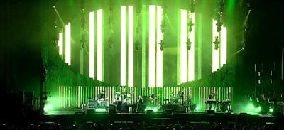Foto da apresentação do Radiohead que aconteceu dia 22 de Abril de 2018, no Allianz Parque, em São Paulo.  A banda toca no palco do Allianz na frente de uma plateia lotada e luzes verdes iluminam o cenário por trás do grupo.