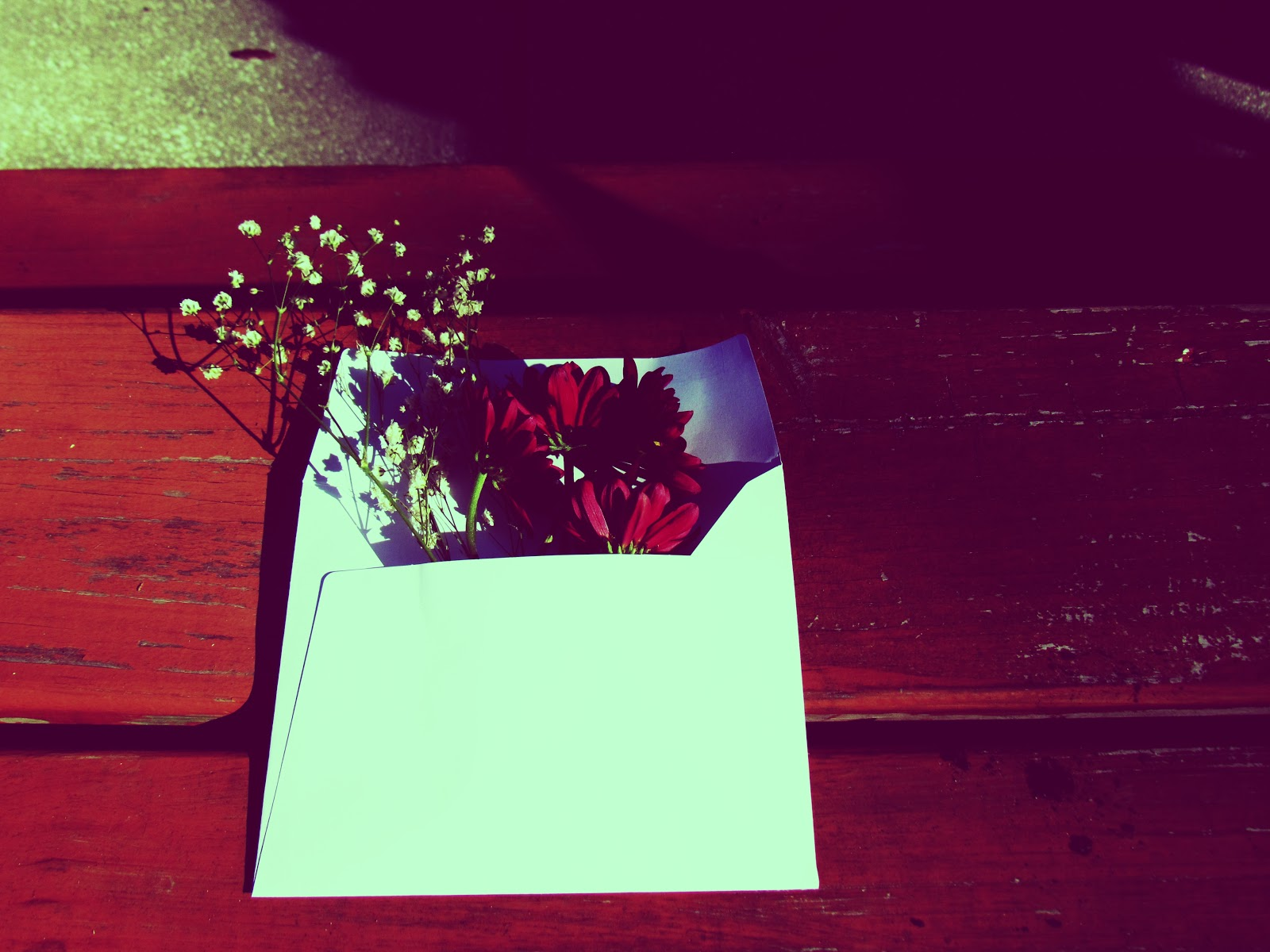 A plain white envelope filled with red carnation flowers for the fall weather and baby's breath flowers on a redwood porch in golden nature
