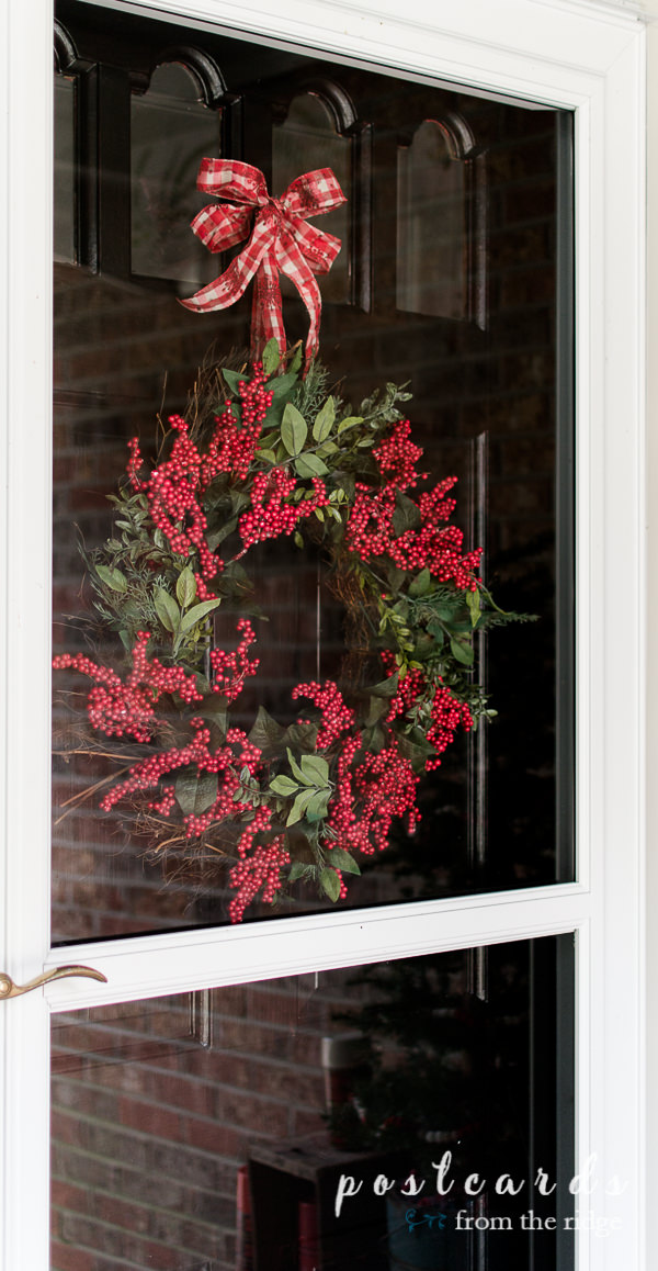 black front door with green and red wreath for Christmas