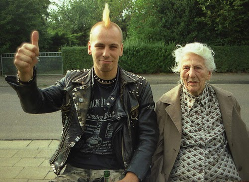 A senior women shares a seat with a punk mohawk young man. Thumbs up.peak Your Mind and other stories of Grandmas and reason. marchmatron.com