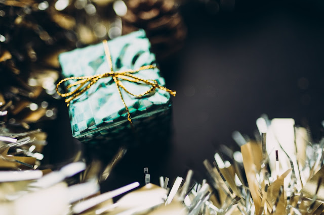 wrapped gift in tinsel Photo by Rodion Kutsaev on Unsplash