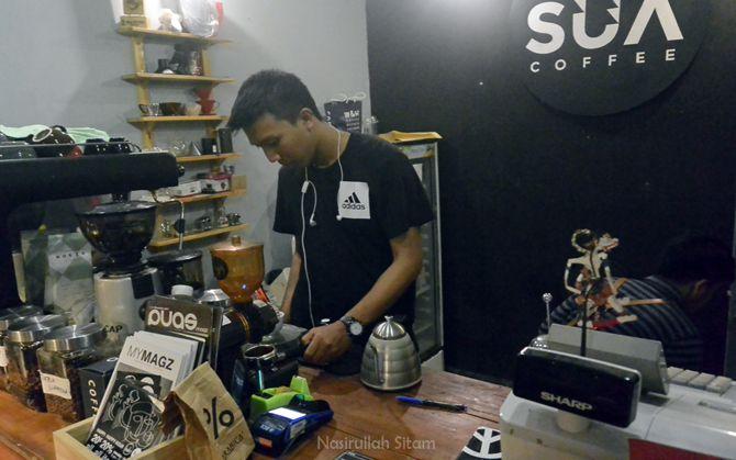 Seorang barista sedang membuat minuman pesanan pengunjung