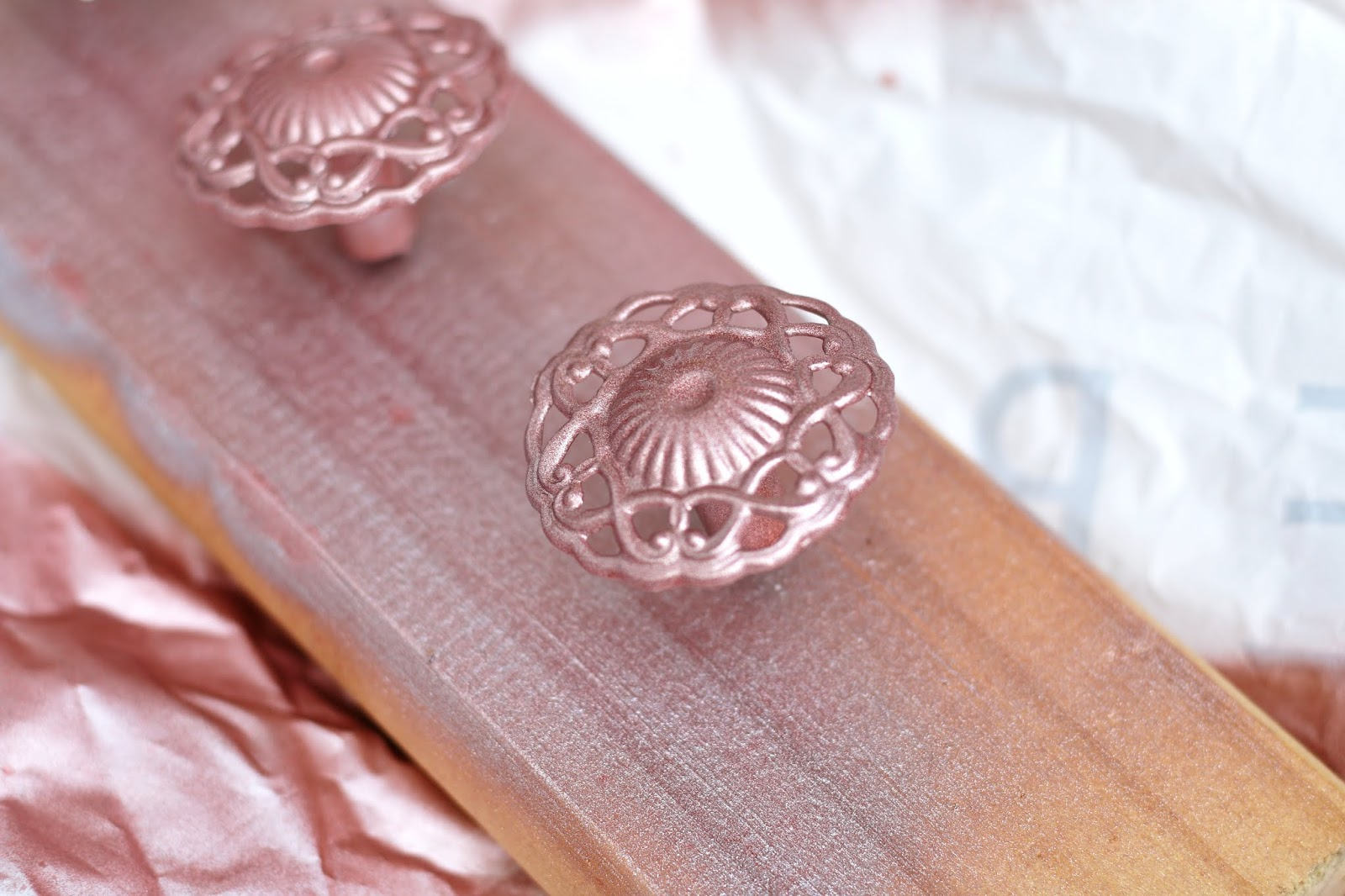 Close up shot on the drawer handle after being spray painted rose gold sitting on the wood with nails