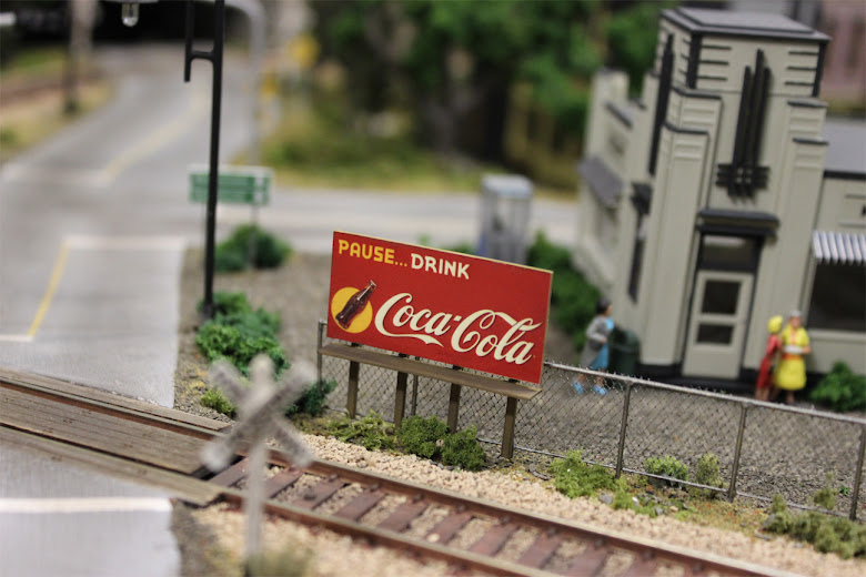 Coca-Cola billboard mounted on a styrene frame and installed along a scratch built chain link fence