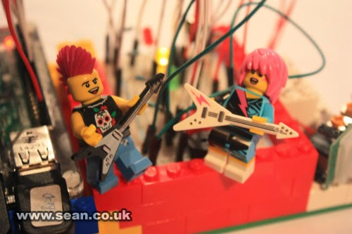 Lego electric guitarist minifigures, male and female, rocking out on a circuit board