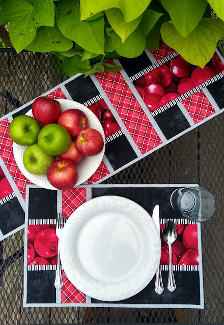 white plate and table setting on red, black and grey placemats with apple print fabric