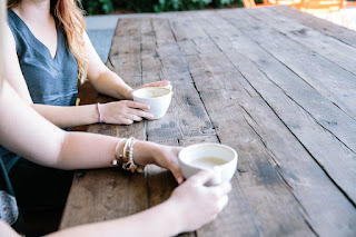 Two people sitting side by side at a park bench table.  We can only see part of them. There are cups of coffee.
