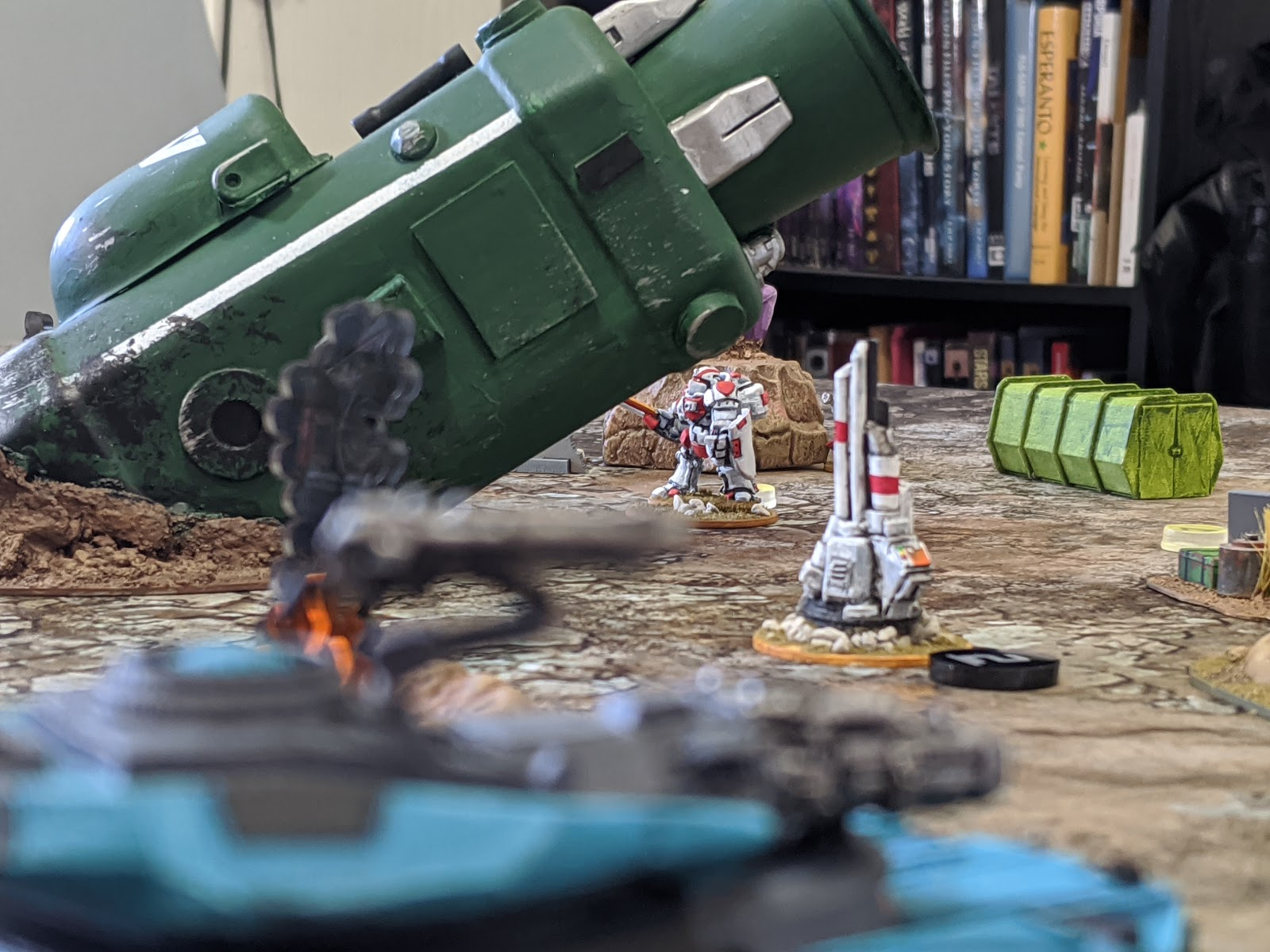 A blue tank sighting in on a white power suit near a crashed green ship.