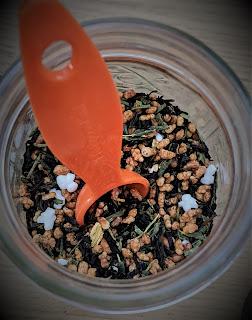 A glass jar of loose leaf tea with an orange teaspoon half in the jar.