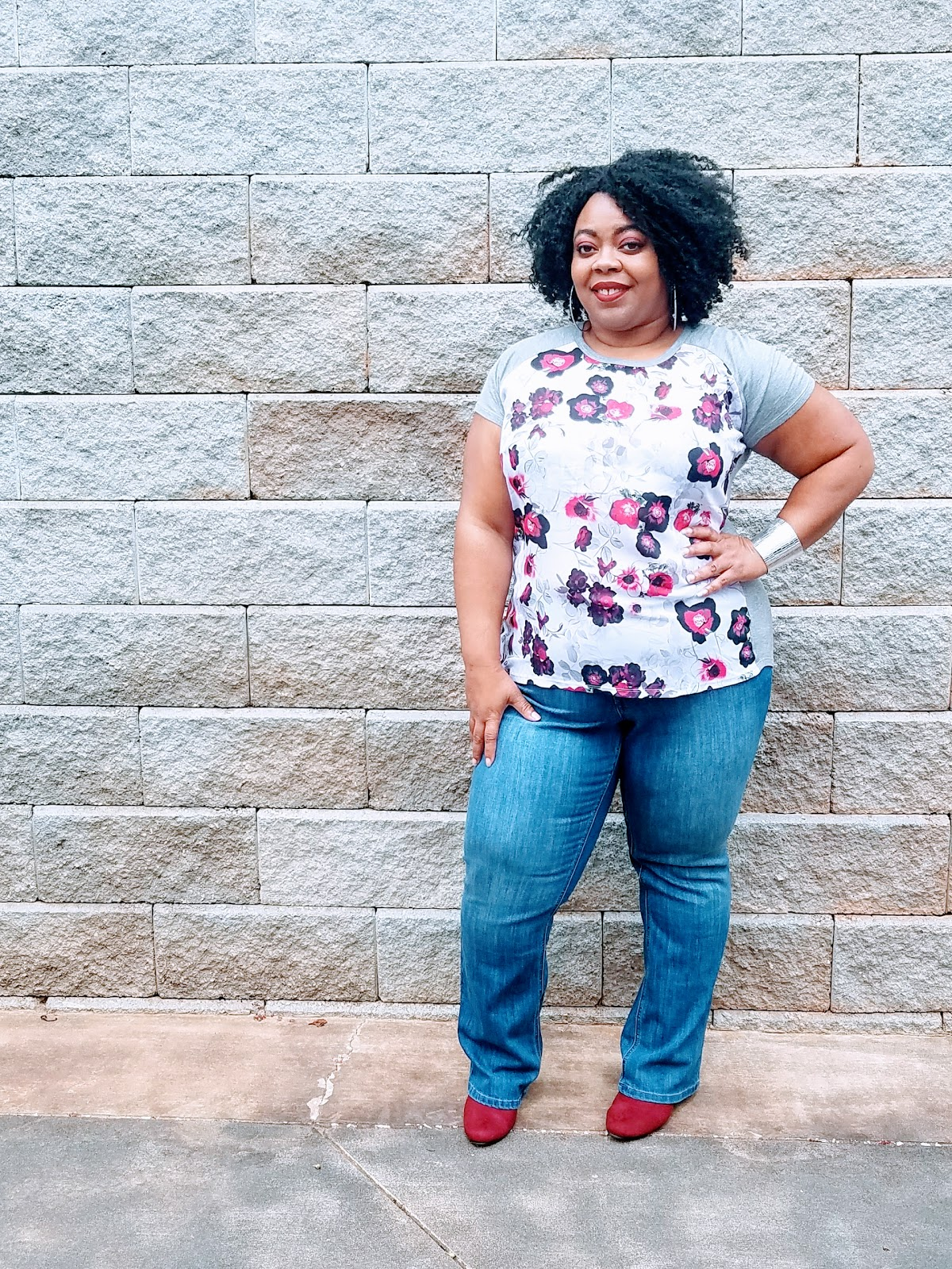 plus size model, curvy girl, natural hair, floral top, faux suede booties, boot cut denim, arm cuff