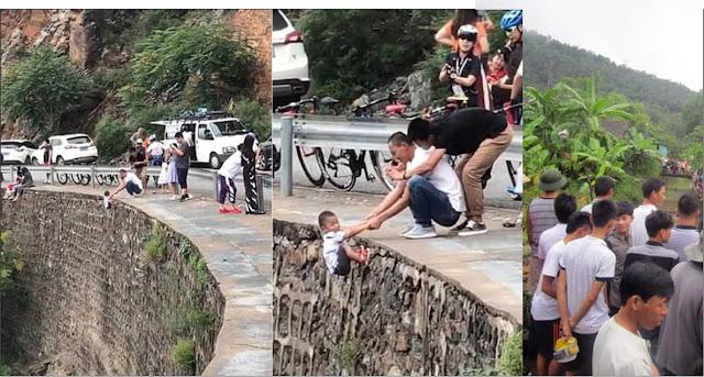 Người cha giữ tay con treo lửng lơ ở vách núi để chụp ảnh sống ảo